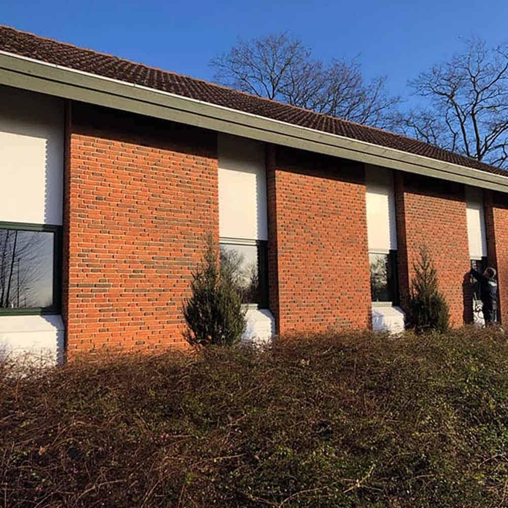 ny udendørs væg med vinduer og mursten
